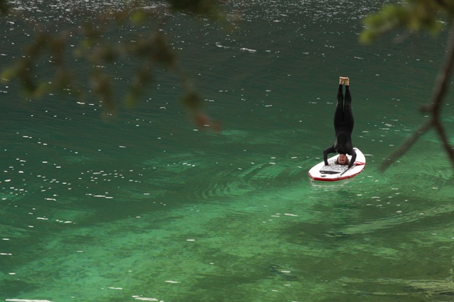 Yoga headstand on paddleboard