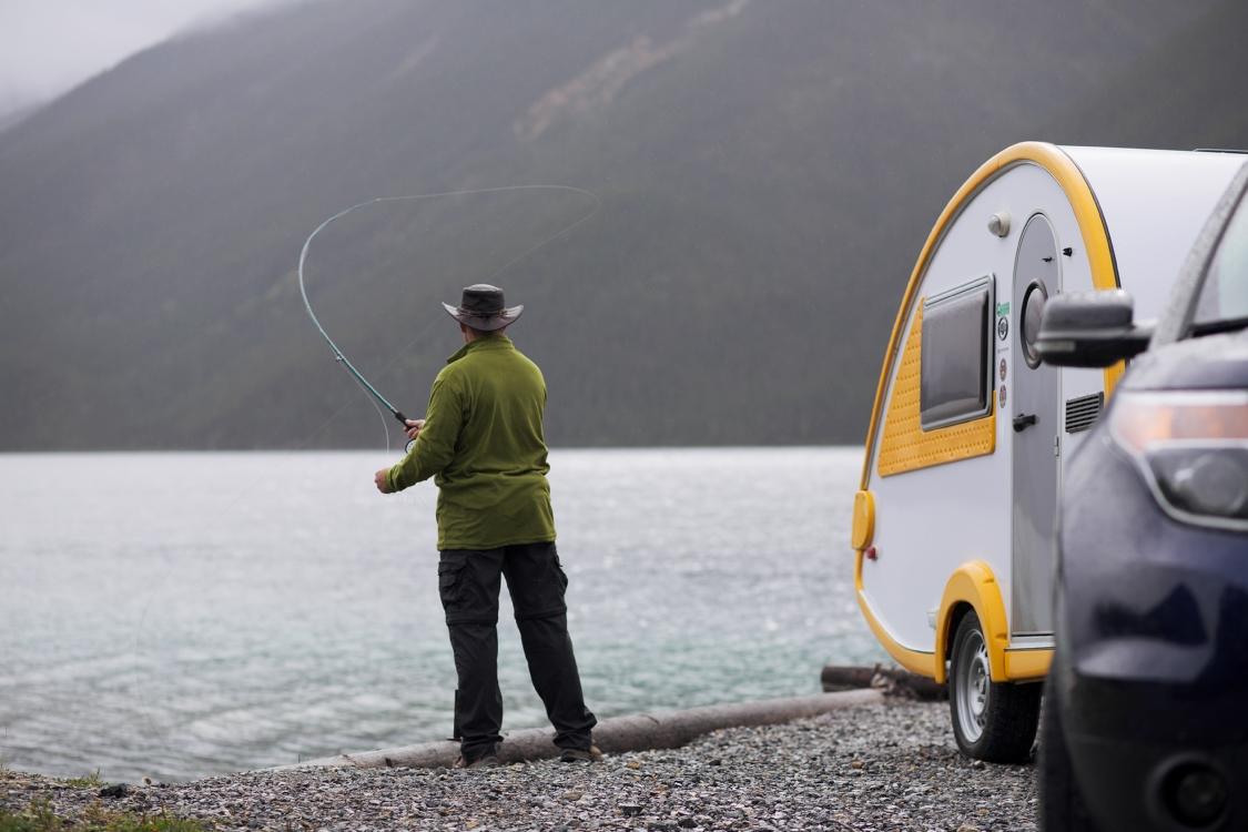 Man Fishing beside his trailer parked at beach