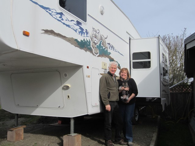 Couple and their dog standing beside recreational vehicle