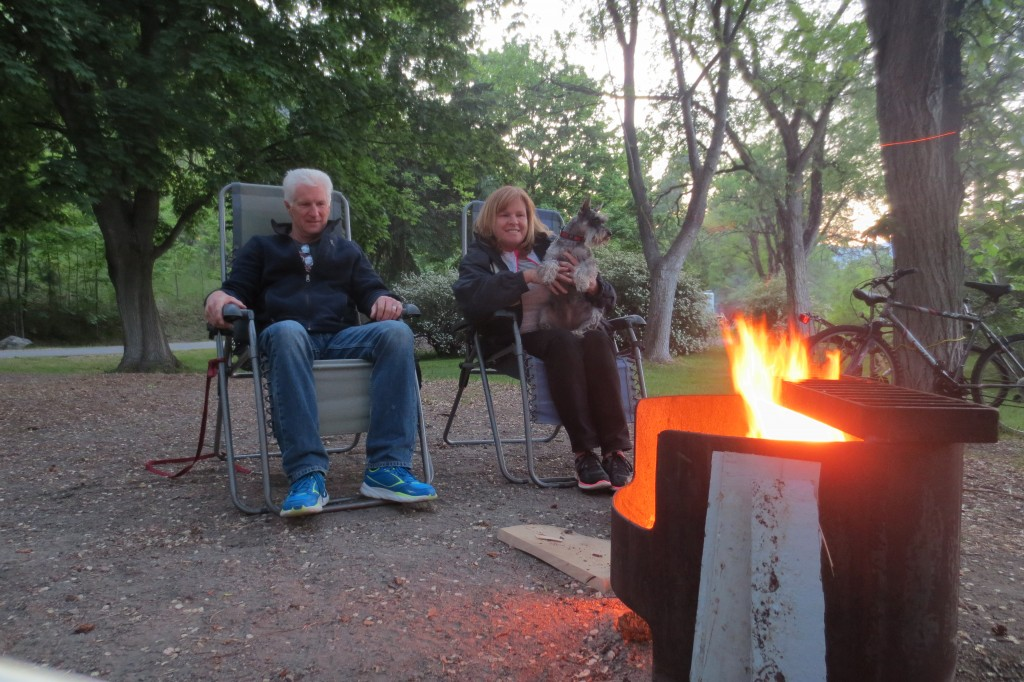 Dog sits on lady's lap in front of the campfire