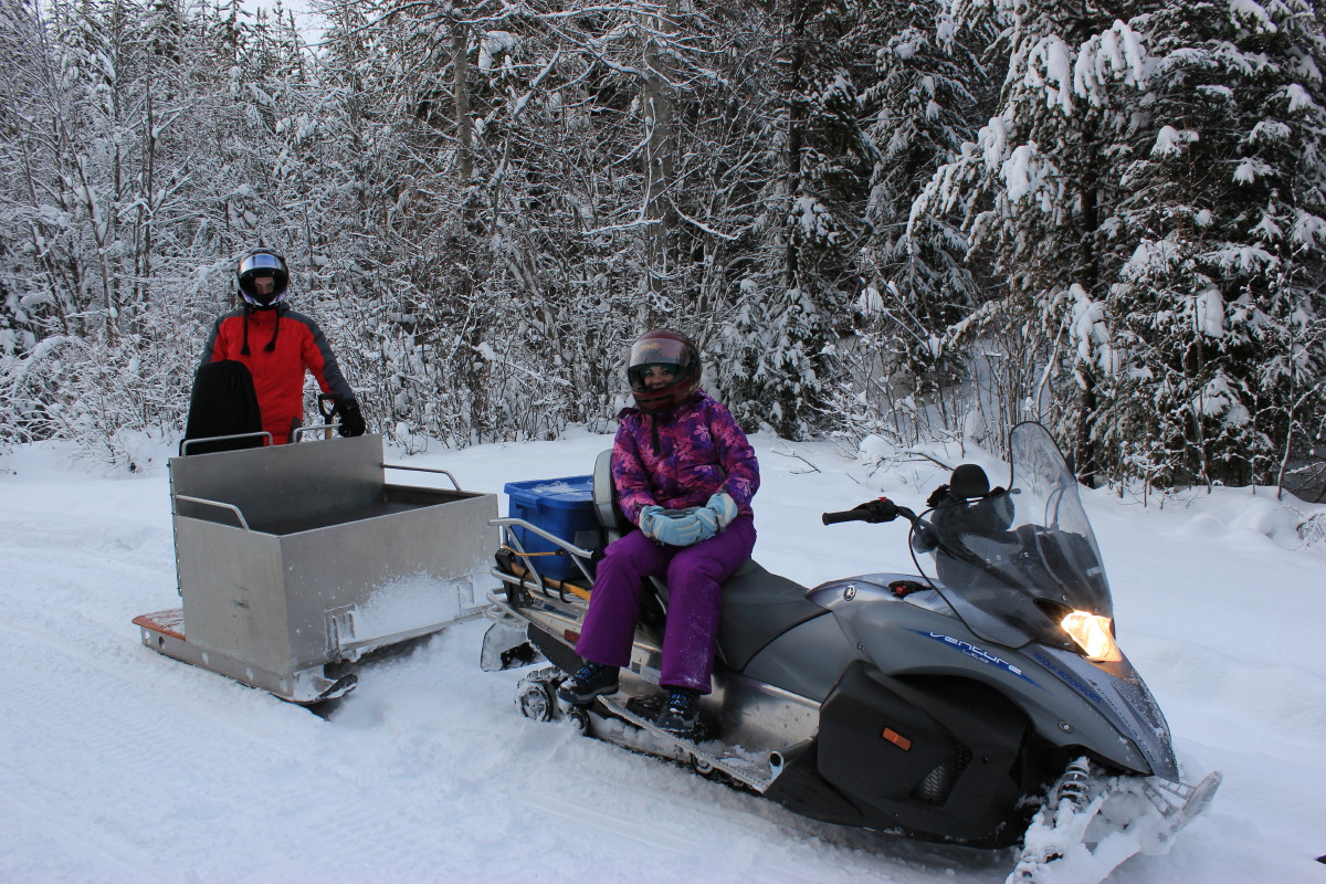 Women and man sitting on snowmobiles