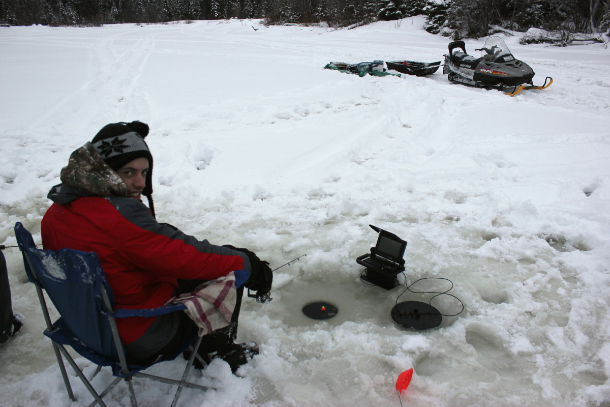 man sitting in chair while ice fishing