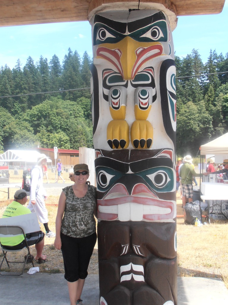 Lady standing beside totem pole