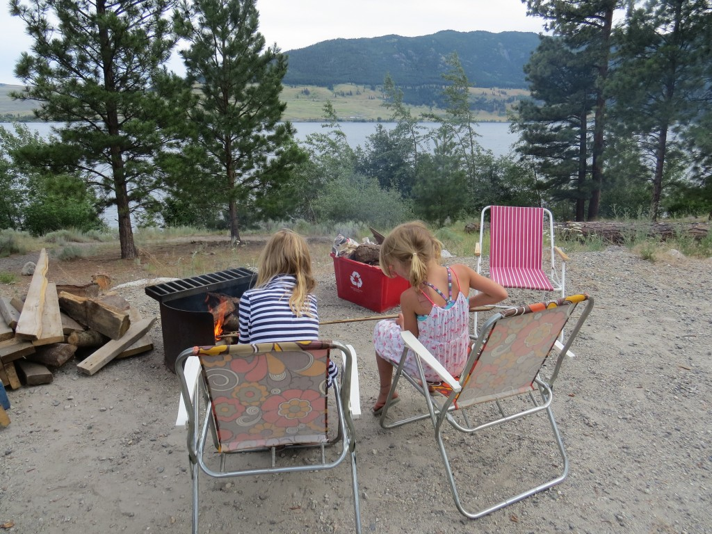 two girls sitting by campfire