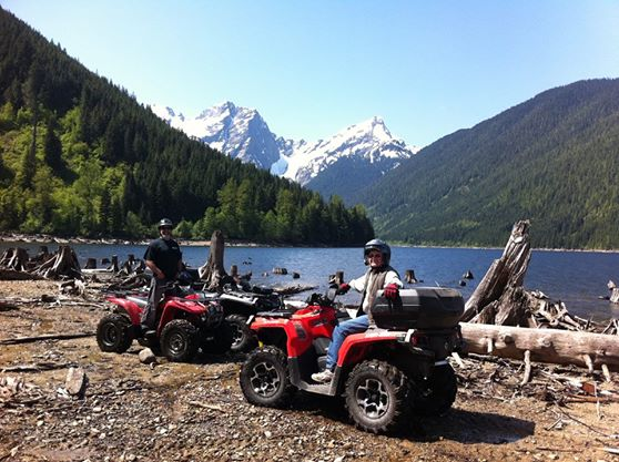 Two ATVers by lake with mountains in background
