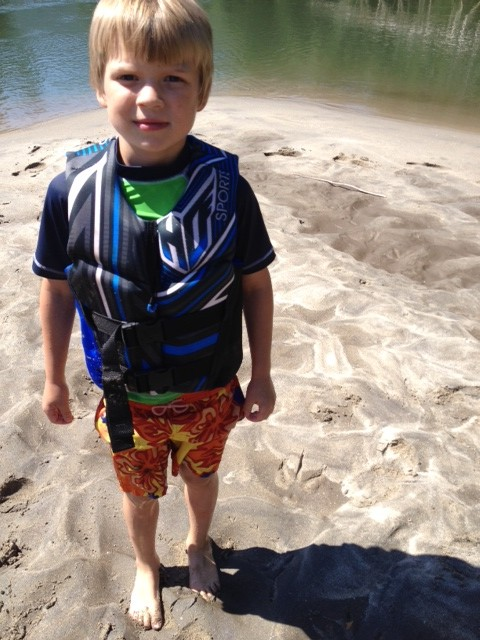 Little boy in life jacket at a beach