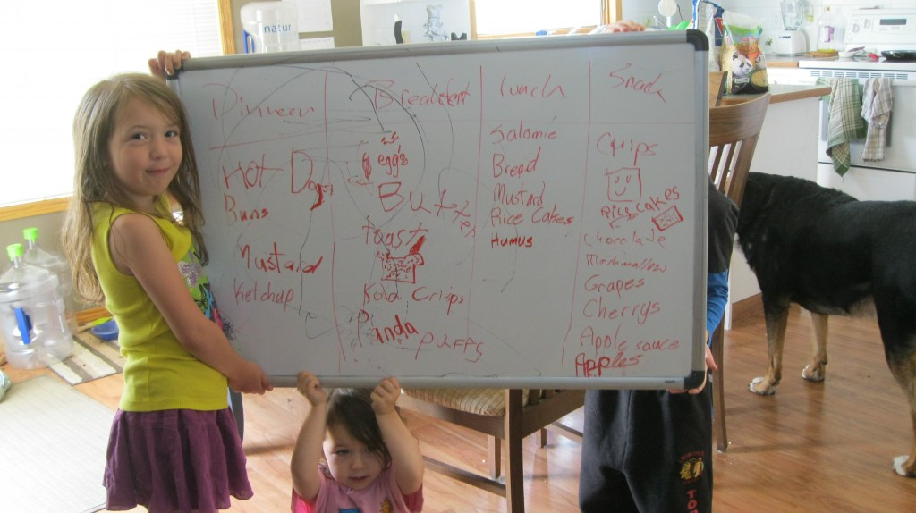 Children holding up a white board with the camping food list