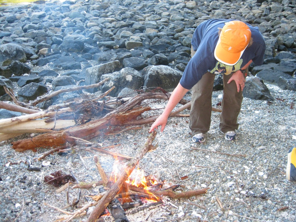 Woman stoking a campfire