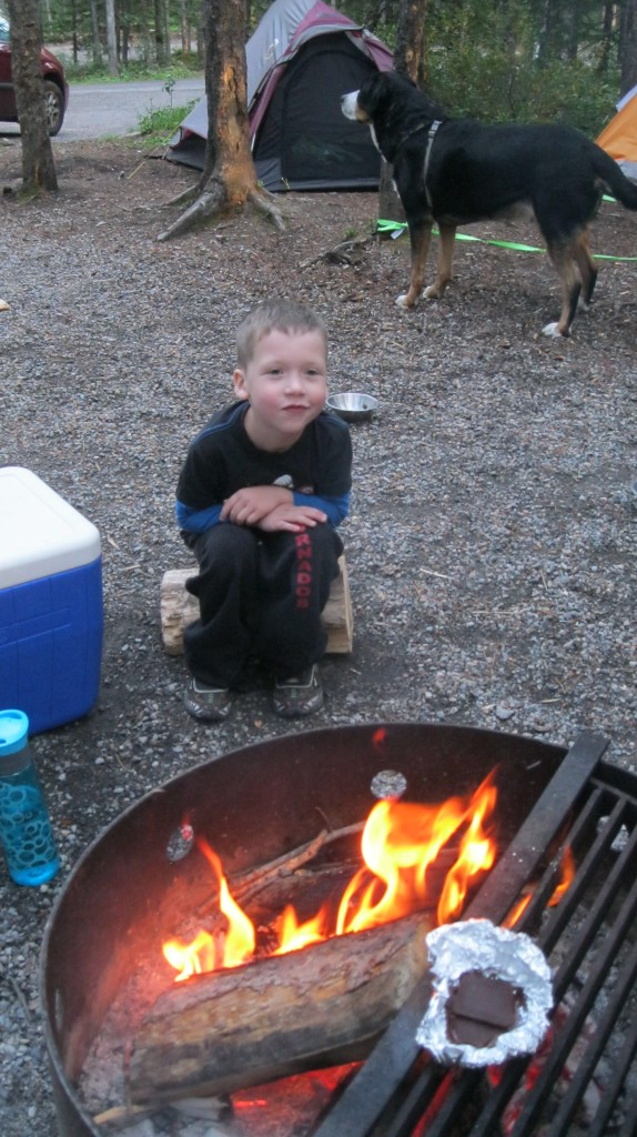 Little boy sitting in front of the campfire