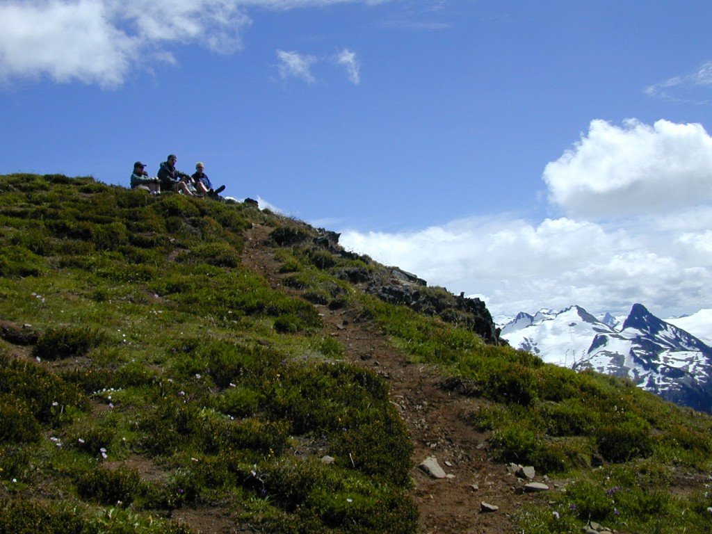 Three hikers resting their legs on top of a hill overlooking the Garibaldi mountain range