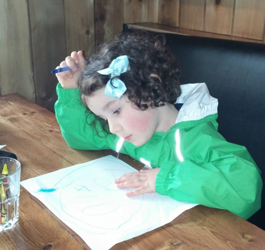 Little girl looking a restaurant menu