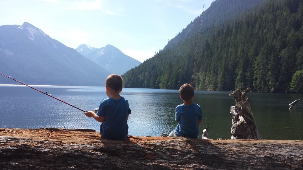 Two boys sitting on a log fishing